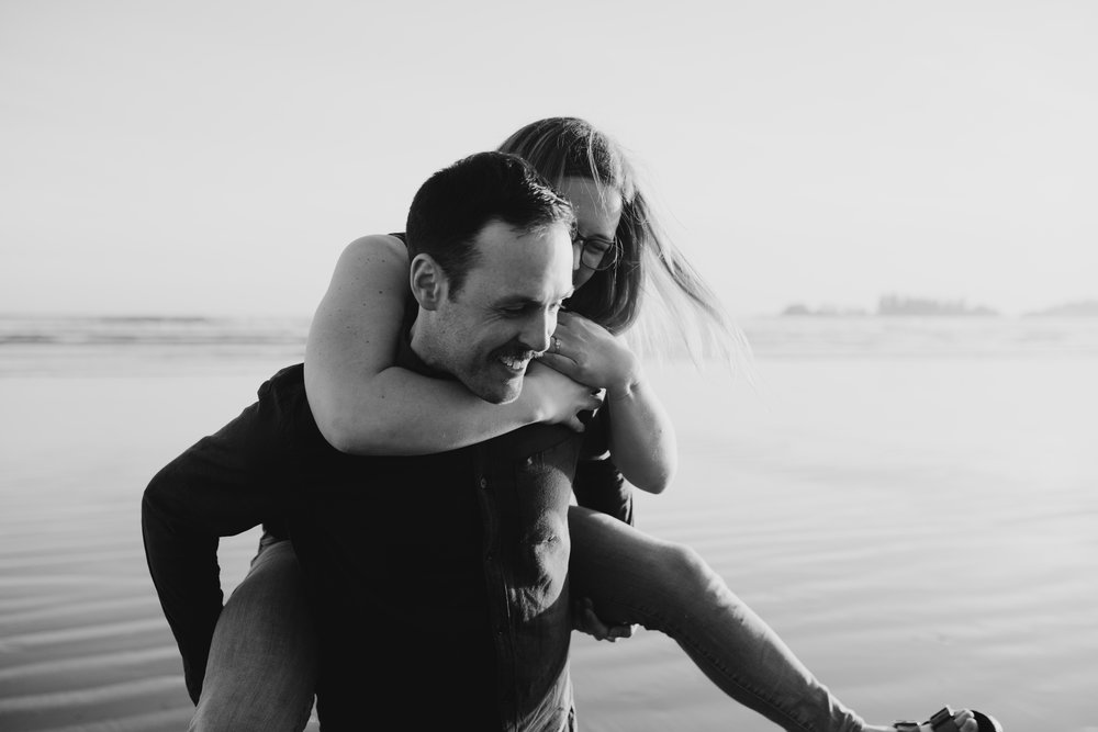 Girl getting a piggy-back from her fiancé, on Long Beach, Tofino, Vancouver Island, black and white image