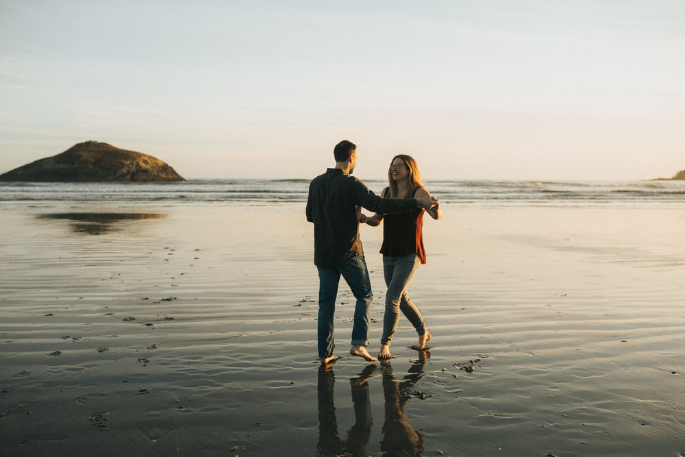 Couple laughing and having fun on Long Beach, Tofino for their engagement session at sunset.