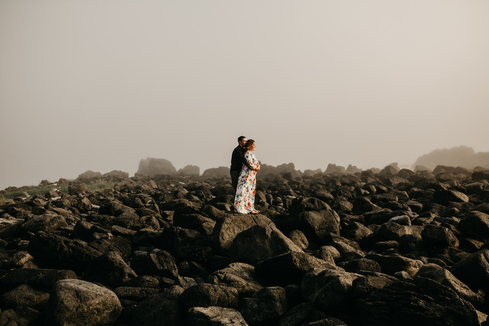 Engaged couple standing on rocks on Big Beach, Ucluelet wedding photographer