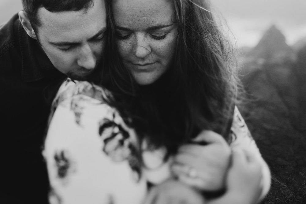 Engaged couple embraces on cliffs Ucluelet wedding photographer