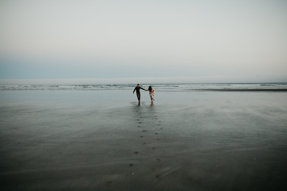 engaged couple runs along Long Beach, Pacific Rim National Park Tofino wedding photographer