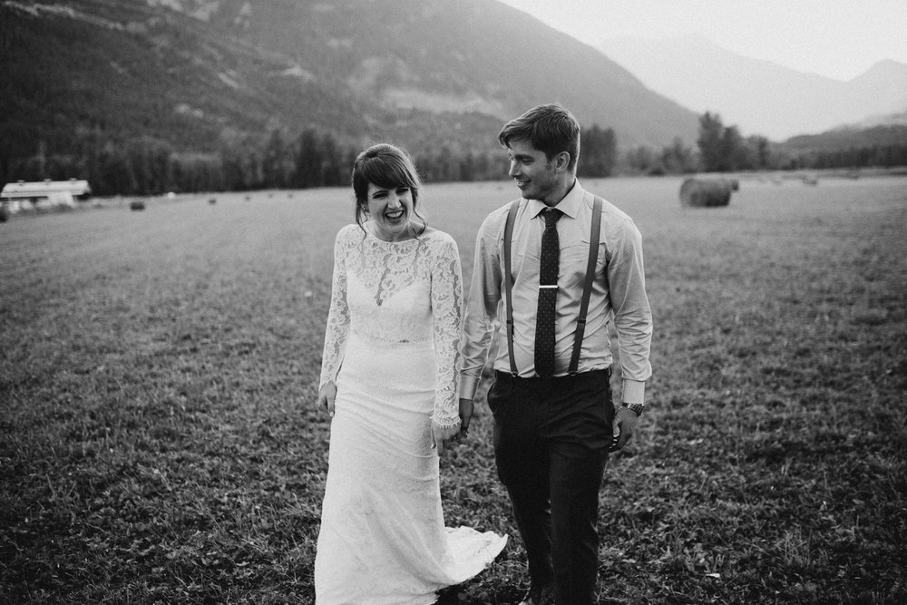 Couple walks hand in hand  in field at Pemberton farm wedding