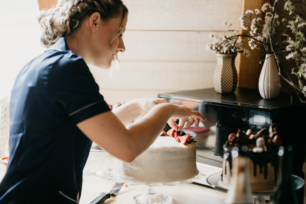 bridesmaid decorating cake at Bird's Eye Cove wedding, Vancouver Island wedding photographer
