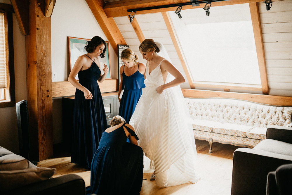 bride putting on dress at Bird's Eye Cove wedding, Vancouver Island
