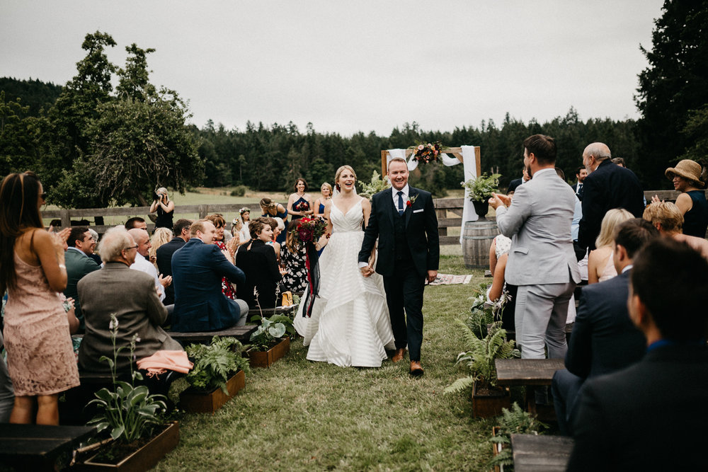 bride and groom walk down isle at Bird's Eye Cove wedding, Vancouver Island