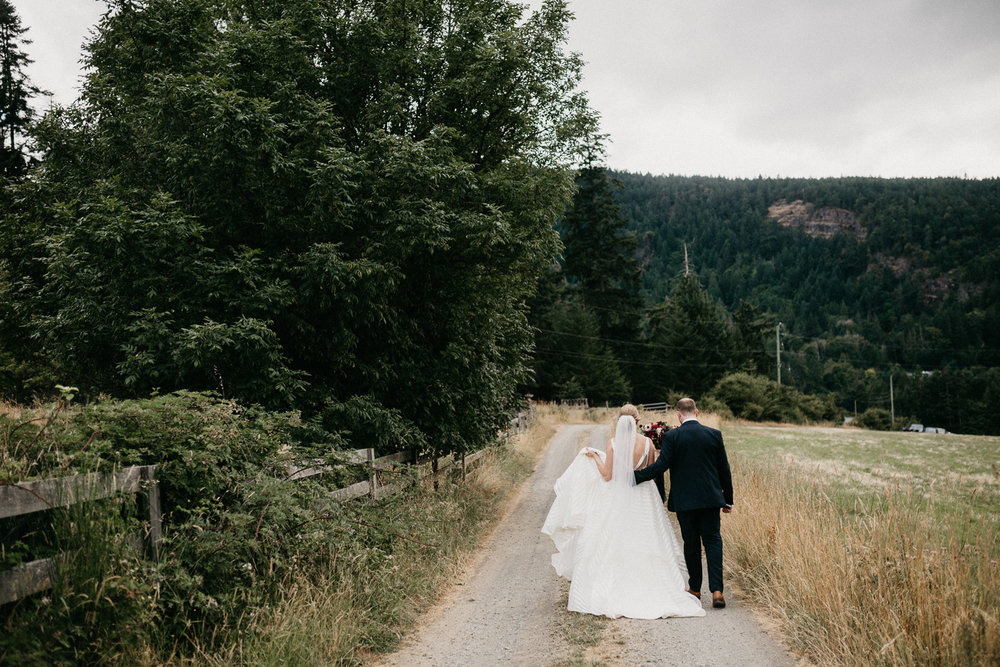 couple walks down lane at Bird's Eye Cove wedding, Vancouver Island
