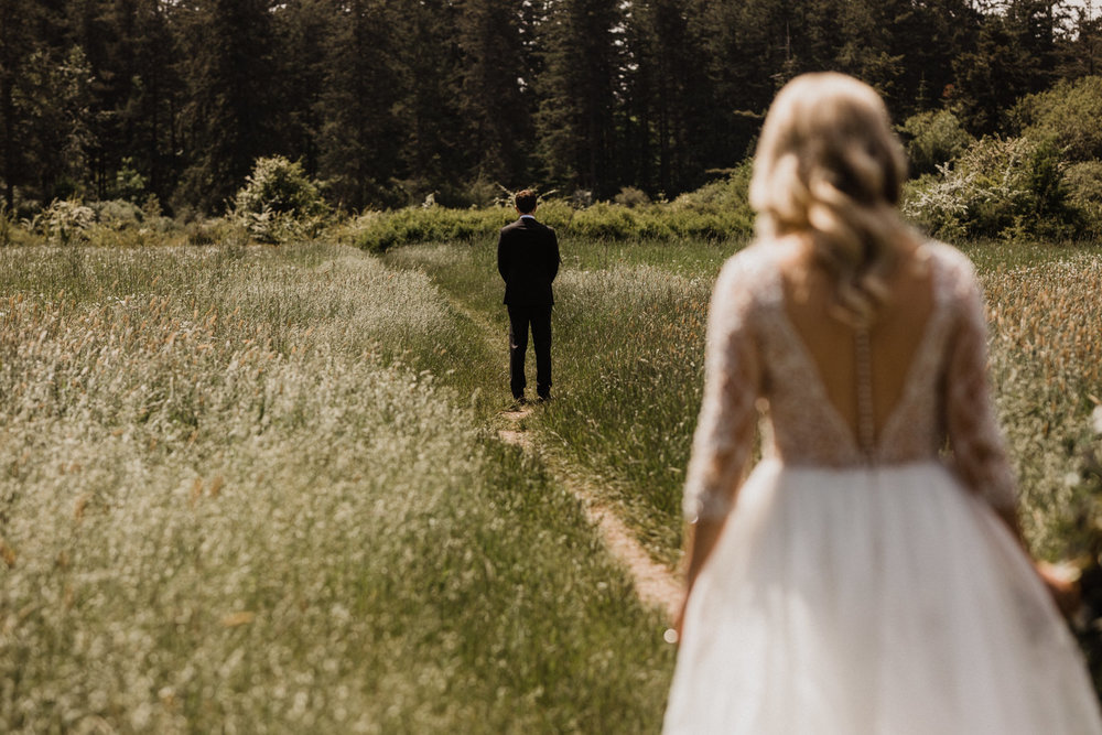 bride walks towards groom for first look at Elk Lake, Victoria Wedding photographer