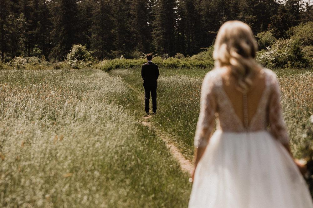 bride walks towards groom for first look at Elk Lake, Victoria Wedding photographer