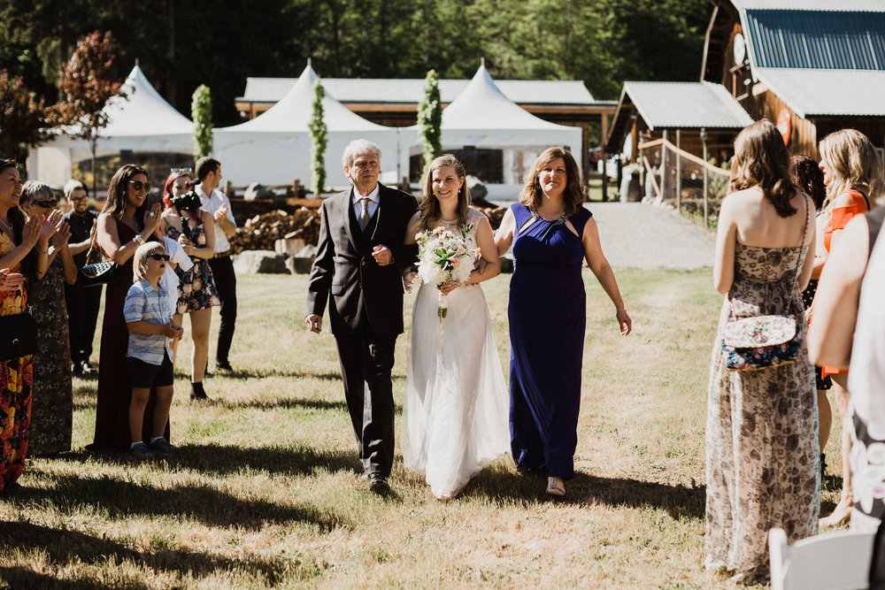 bride walks down isle with mom and dad vancouver island wedding photographer