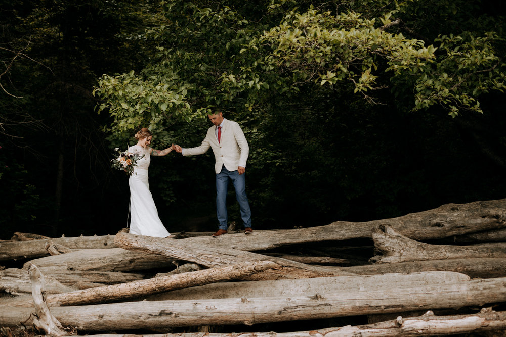 groom helps bride across driftwood mount doug beach Victoria elopement photographer