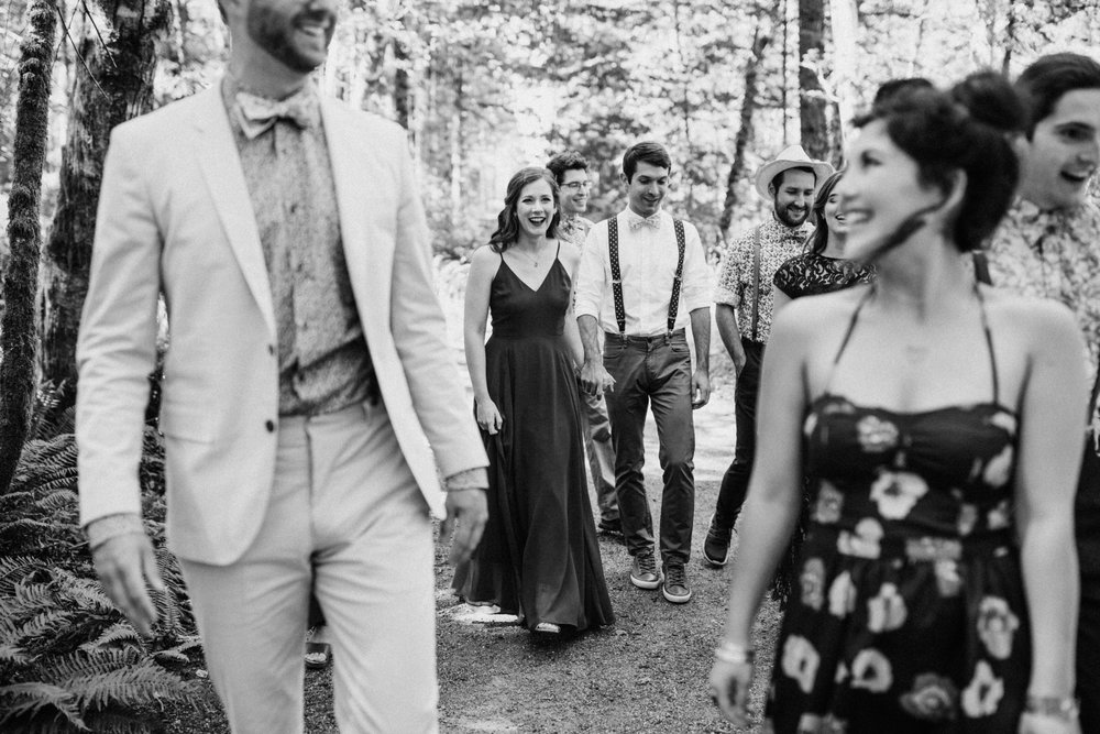 Bridal party walks through woods