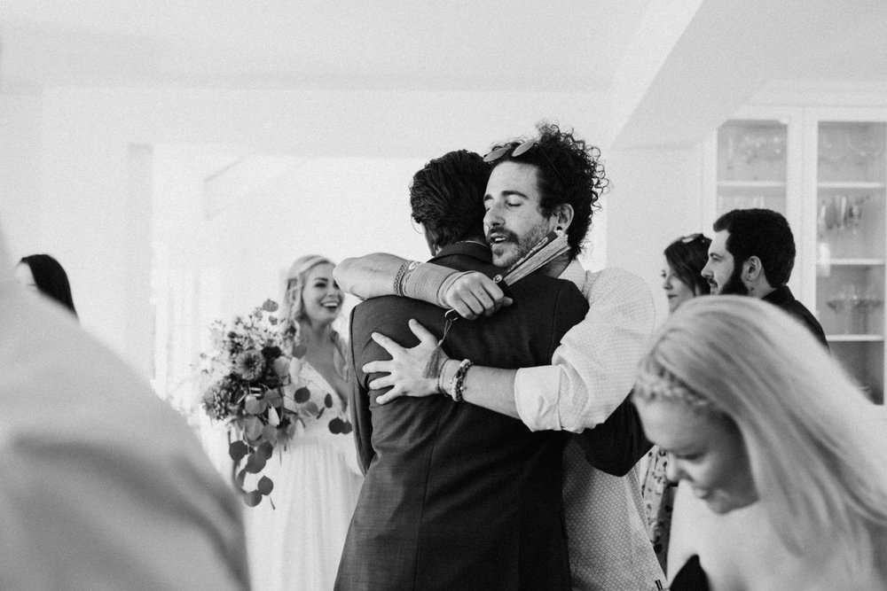 groomsman hugs groom West Vancouver backyard wedding photographer
