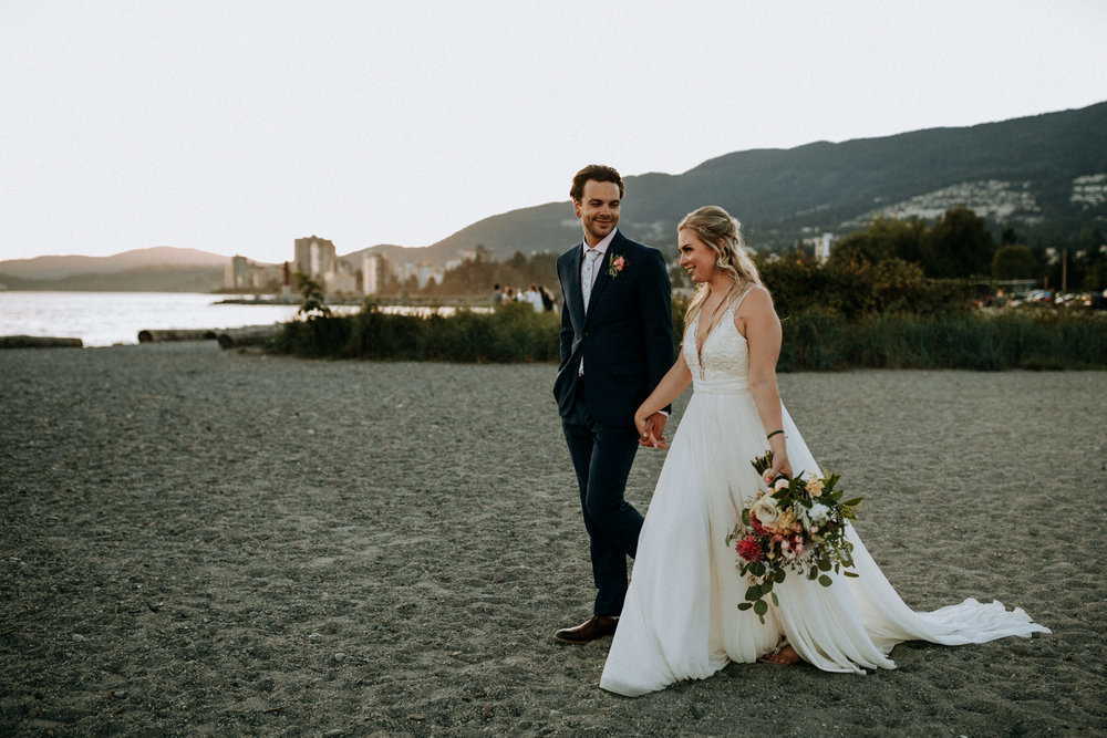 couple walks on Ambleside Park, Vancouver intimate wedding photographer