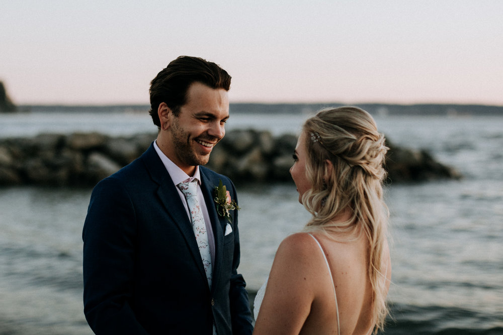 groom smiles at bride sunset Ambleside Park West Vancouver Wedding Photographer