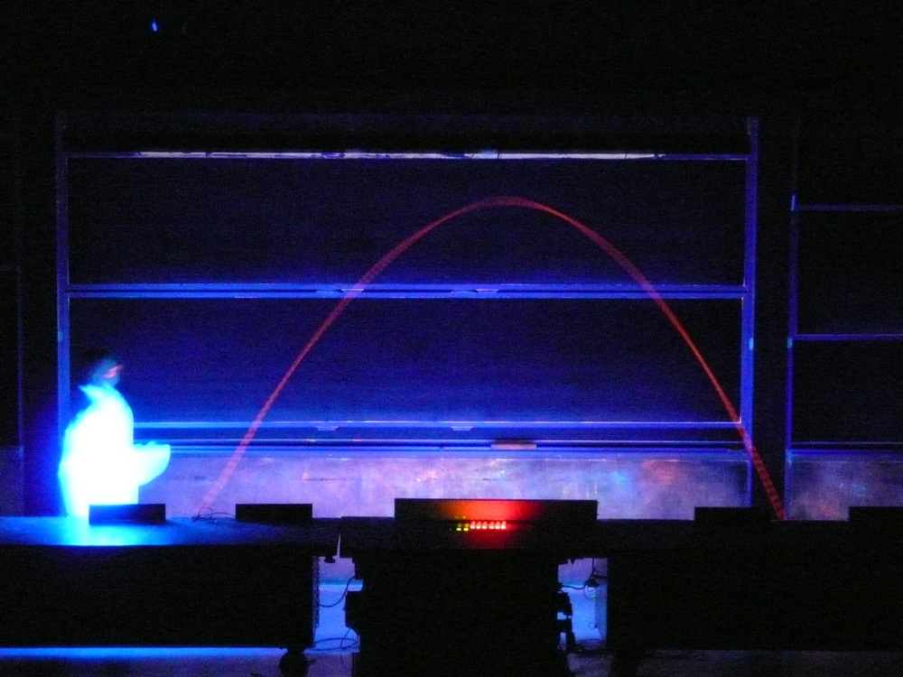 An orange arc showing the smooth center of mass trajectory of a thrown tennis racquet