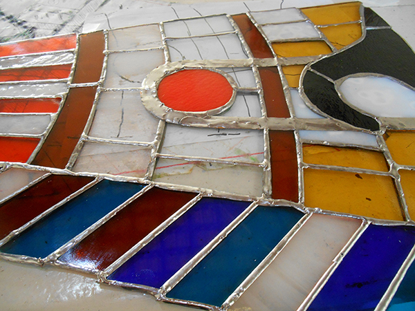 One fully soldered stained glass panel. The uneven edges will be blocked by the stainless steel frame.