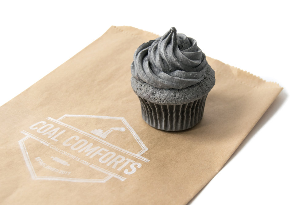 "Coal Comforts  is a pop-up art ""bakery"" in which the familiar-looking treats on offer are not what they appear— they're inedible simulacra made of ash from burned coal."