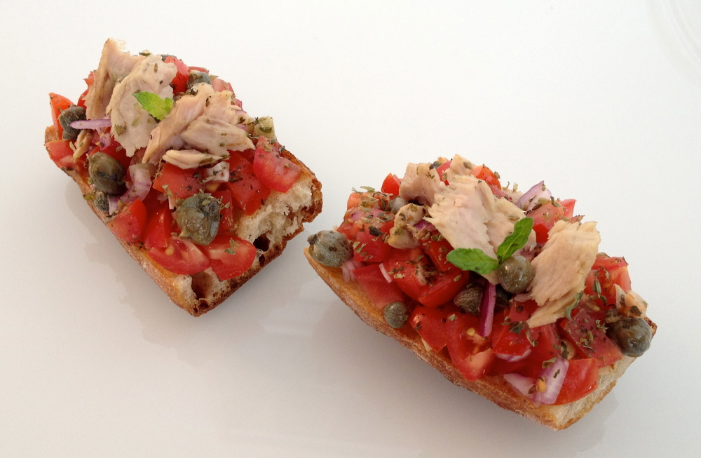Toast topped with cherry tomatoes, capers from Salina, homemade tuna, oregano, mint, and olive oil
