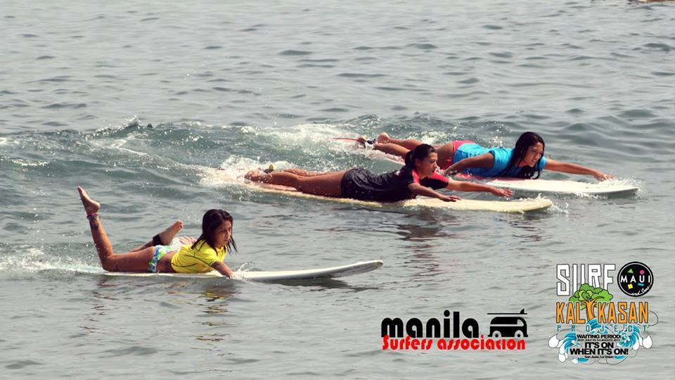 Paddling hard with Mylene Dizon and Bianca Arambulo at the Maui and Sons Surf Kalikasan surfing competition. Photo by Miccah Doctolero.