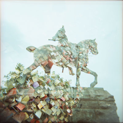 Double exposure (Holga 120GN and Kodak E100VS). My first layer was the statue with a very light background. My second layer was a shot of love locks on a bridge. It creates a silhouette with a pattern filling. You can see that the locks from the second layer do not show in the almost white sky from the first layer.