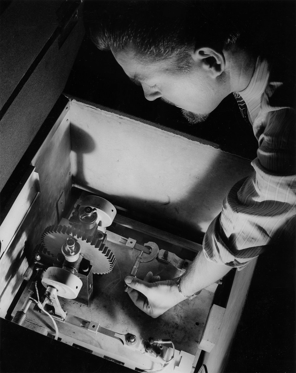 "This combination oven-refrigerator that varies temperatures from 50 degrees below zero to 200 degrees above has been constructed at the Westinghouse Research Laboratories to test the strength of Micarta plastic used in making engine gears and aircraft parts. Frank Cassel, Westinghouse research engineer, is shown measuring the dimensions of a Micarta test piece in the oven-refrigerator before beginning a ""fatigue"" test. This Micarta stock, along with a similar one to its left, will be vibrated up and down 15 times every second, day and nights for as long as three months. While one end of the plastic stick is held stationary, the other end is moved up and down rapidly by the rotating arm and wheel. The amount of load applied and changes in the flexibility of the plastic are measured by the wire resistance ""strain gauge"" at the stationary end of the vibrator. Cooled by dry ice and heated by electric coils, the oven-refrigerator provides extremes of cold and heat to aid in the development of plastic equipment that gives maximum performance at any working temperature."