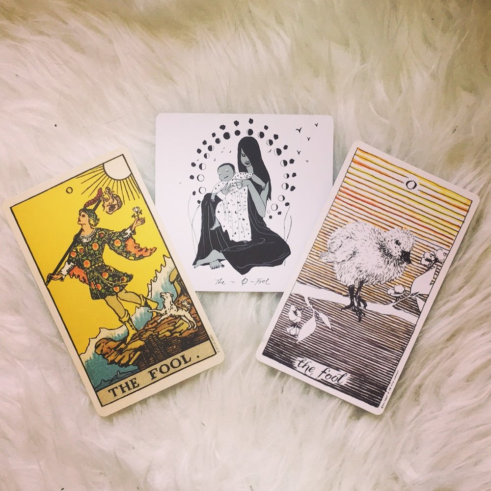 Cards shown here (L-R): the Rider-Waite Deck illustrated by Pamela Coleman-Smith, the Dark Days Tarot illustrated by Wren McMurdo, and the Wild Unknown Deck illustrated by Kim Krans.