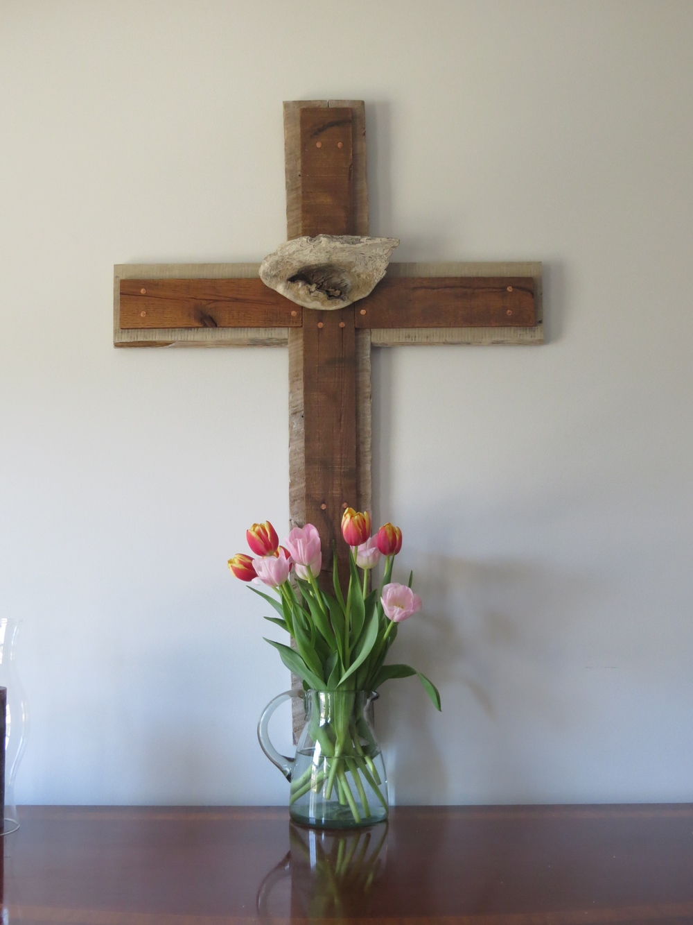 This cross proudly rests on the wall in our dining room. It's the one my husband built for me to be on the altar overlooking the water on our wedding day. I like to show off God's handiwork in his hands. And those are the tulips I've been bragging about...