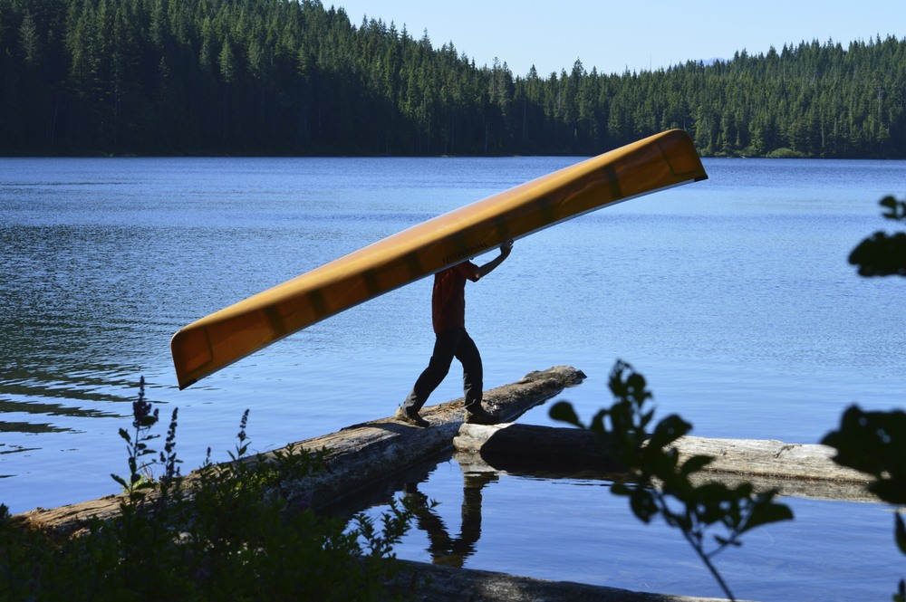 Portaging the canoe into a tricky put-in spot on Surprise Lake