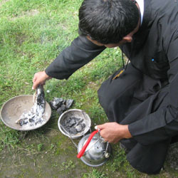 Fr. Blas (one of the native priests) prepares charcoal to put into a censer. The communities face a severe lack of quality liturgical items.