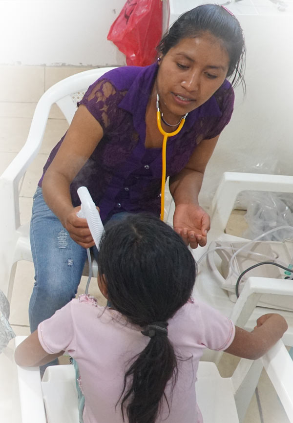Juana gives a nebulizer treatment to a child with asthma