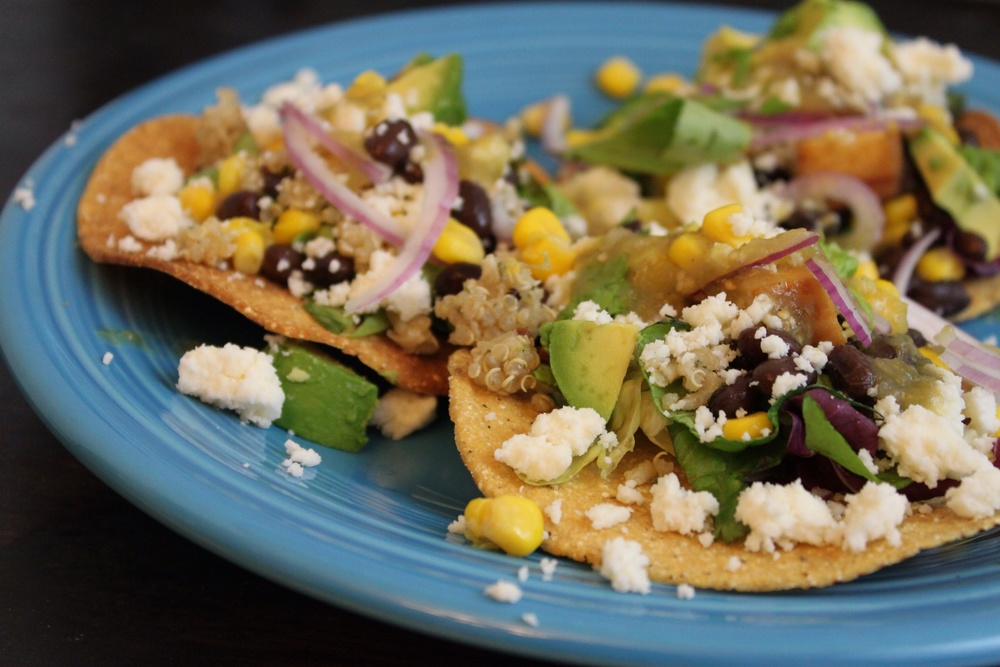 Vegetarian tostadas with quinoa, black beans, cotija, avocado, spinach, tomatillo salsa, corn and red onions.