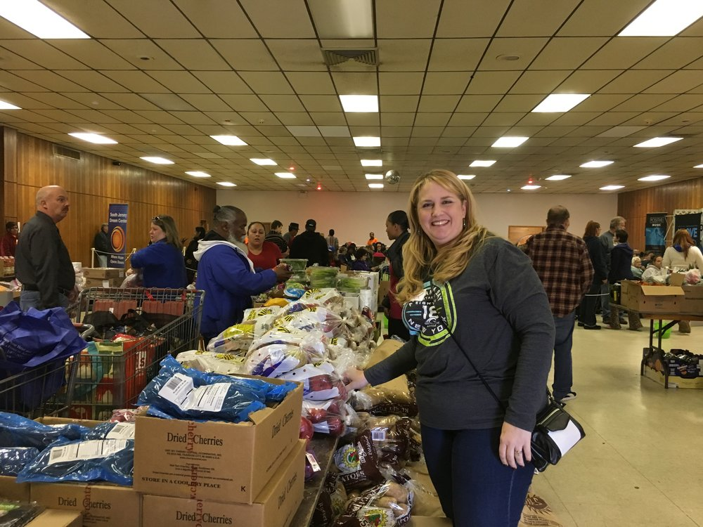 Volunteer Angela Horn-Worrell of Johnson Matthey assists guests with bags of fresh-picked fall fruit and vegetables from New Jersey Farmers Against Hunger.