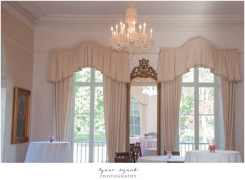 floor to ceiling windows and chandelier inside the Commanders Mansion set up for a wedding