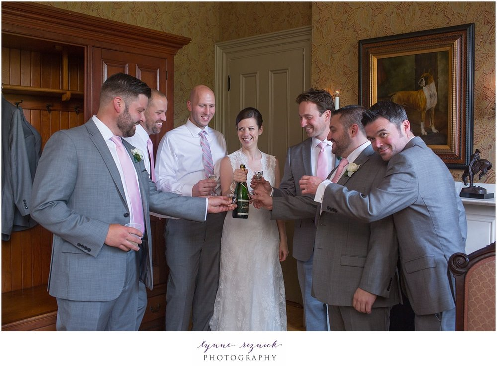bride and groom toast with groomsmen in a well appointed room in the historic commanders mansion in Watertown MA