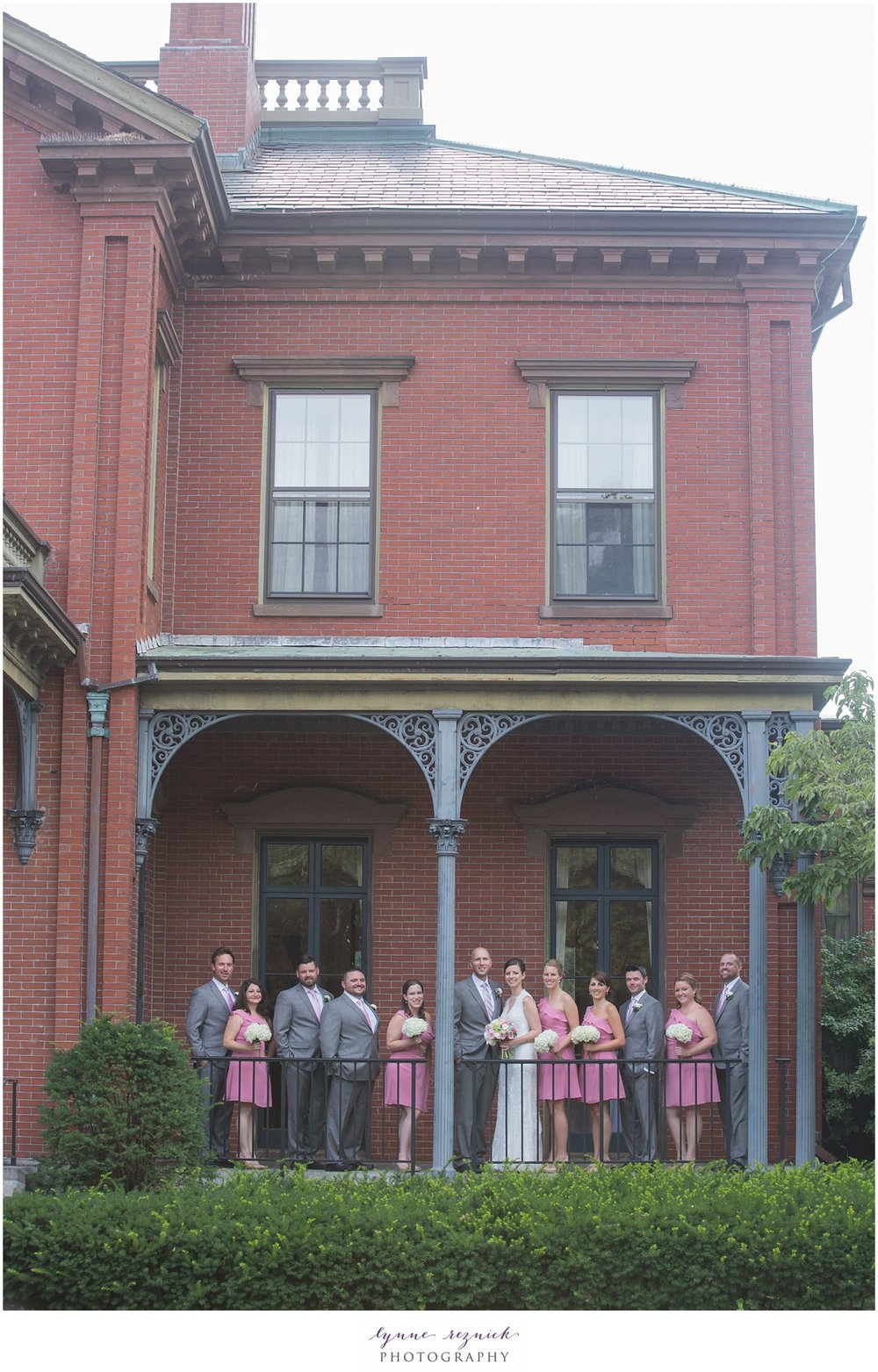 bridal party poses on the porch at the Commanders Mansion during a summer wedding