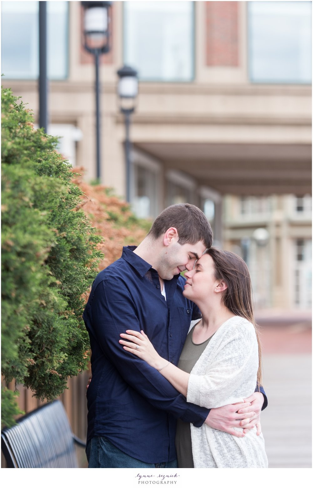 sweet engaged couple snuggles behind Boston Harbor Hotel