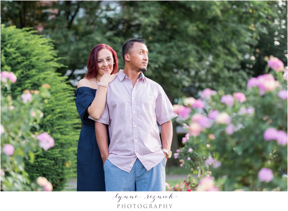 lush flowers surround engaged couple for summer portraits in Boston Public Garden