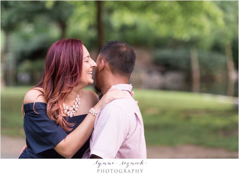 whispering sweet nothings to her fiancee in sunset engagement portraits at Boston Common