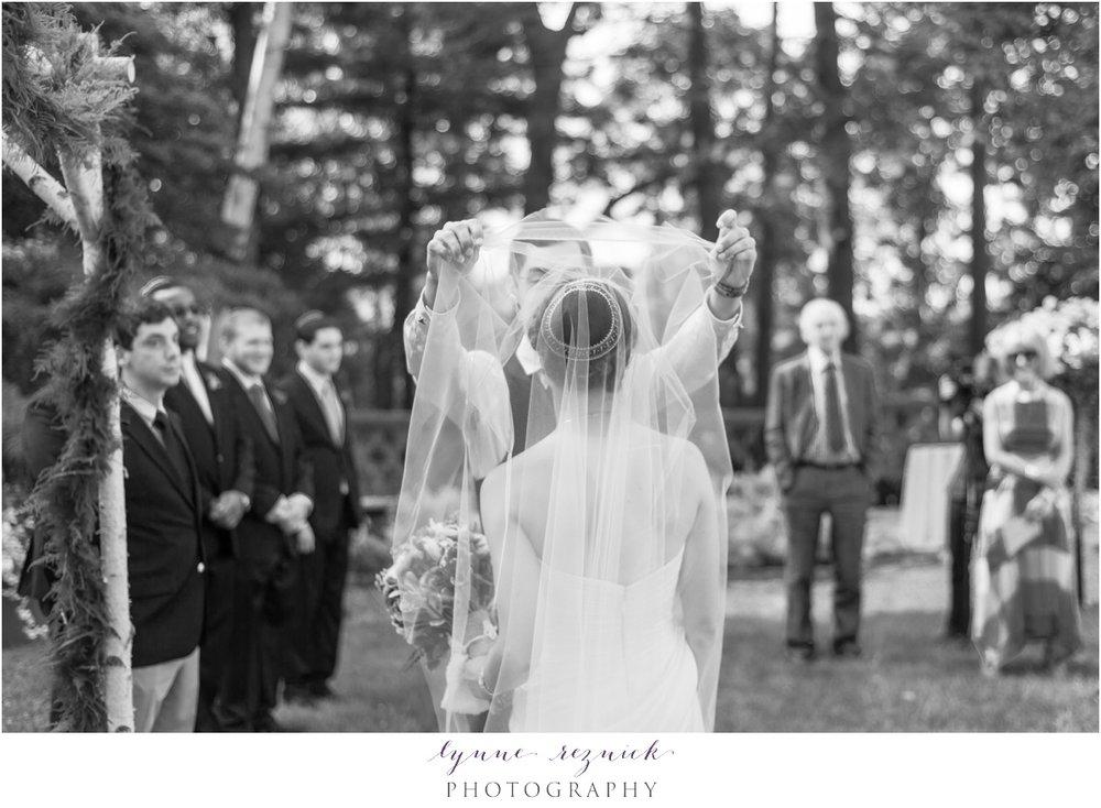 groom lifts bride's veil at start of bradley estate wedding ceremony