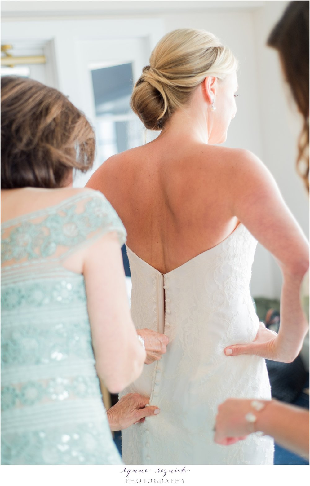 Mom and sister help bride get ready for ceremony at the belle haven club in greenwich CT
