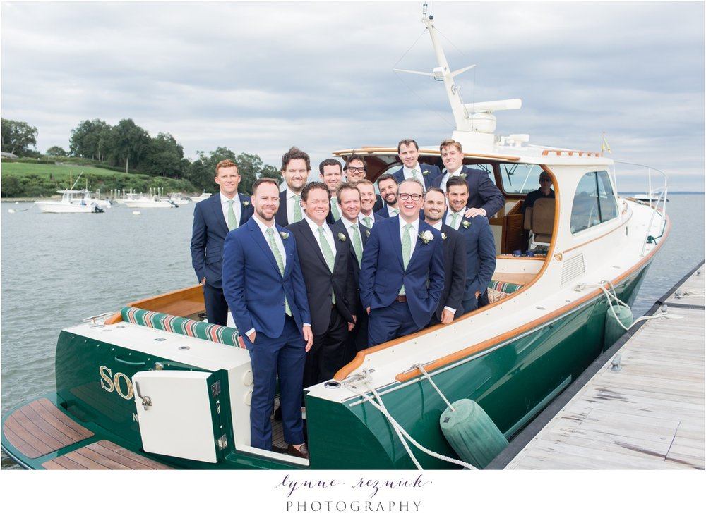 groom and groomsmen on boat at belle haven yacht club
