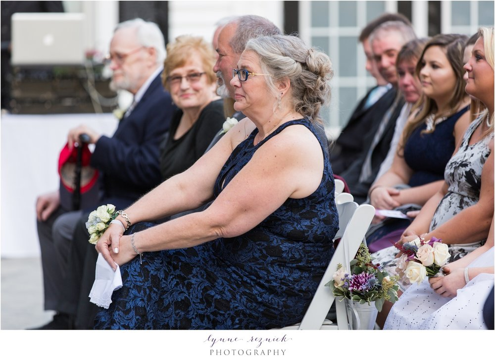 mother of the groom looks on at saphire estate wedding ceremony