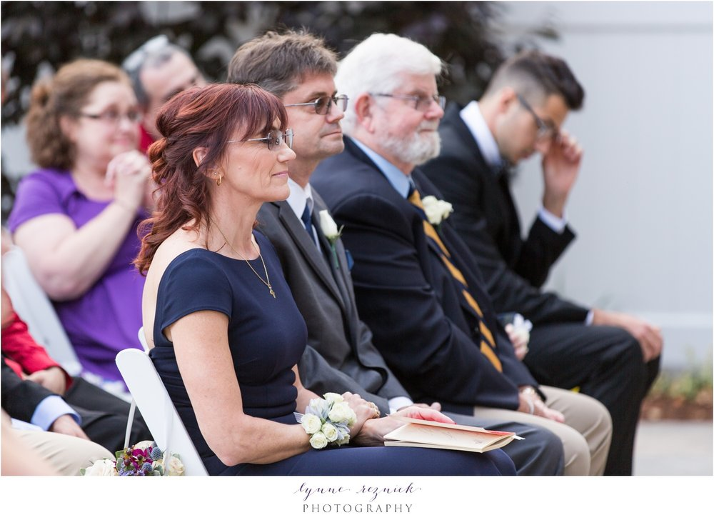 mother of the bride looks on at saphire estate wedding ceremony