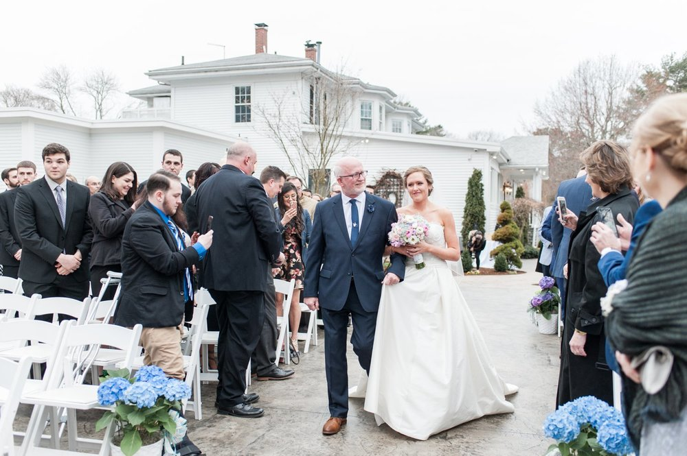 bride and dad walk down the aisle at outdoor ceremony at saphire estate