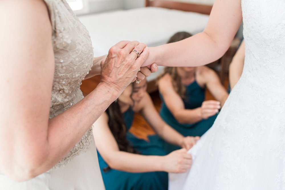 bride and mom hold hands at rustic chic lake spofford wedding in New Hampshire