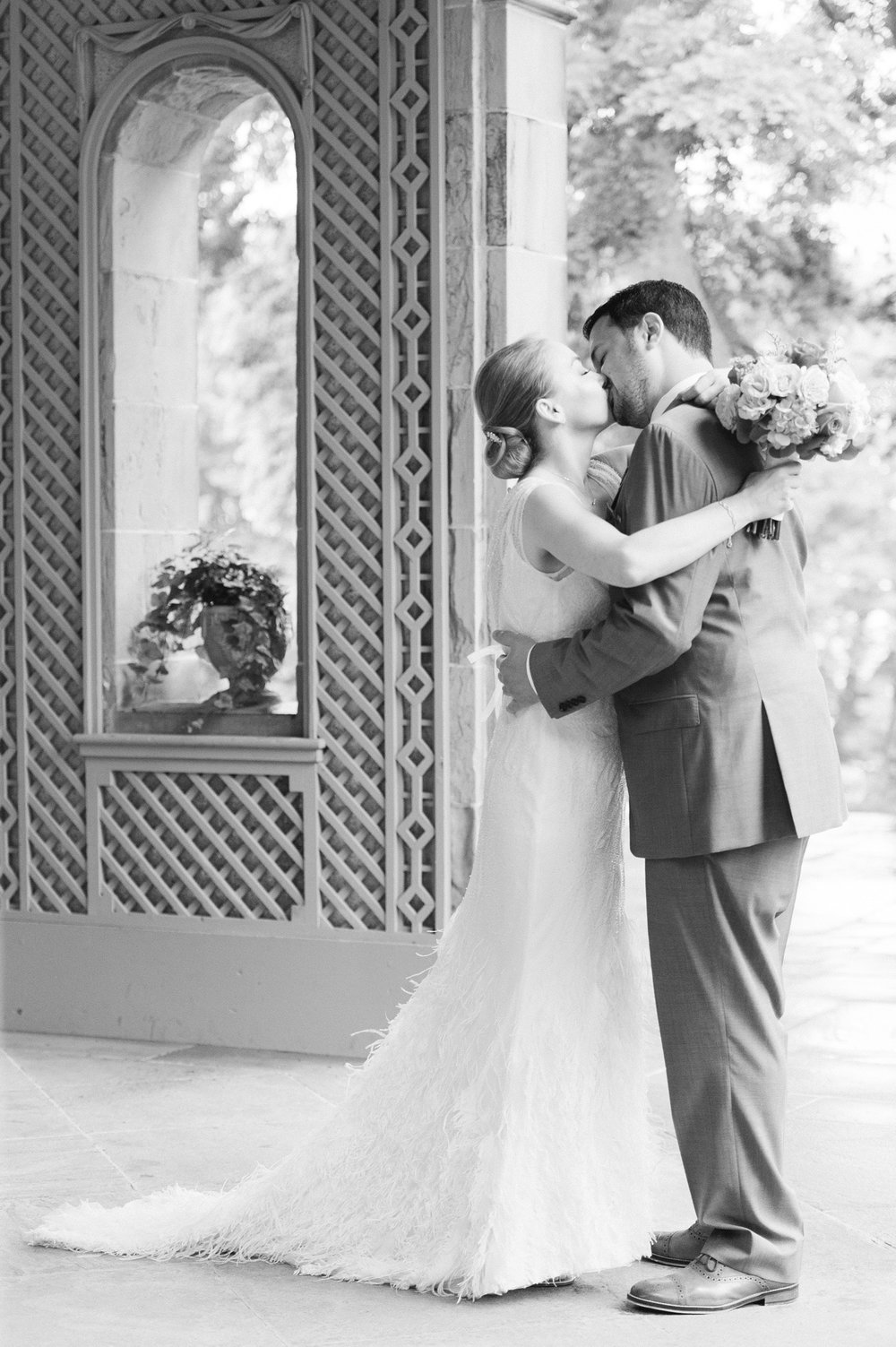 glen manor house wedding in rain first look under terrace in spring with blush accents and bride in rosa clara dress with feathers black and white