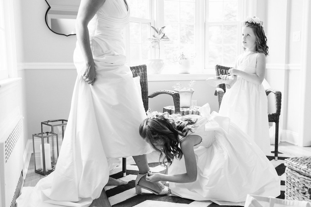 flower girls help the bride put on her jewel by badgley mischka shoes for her fall wedding