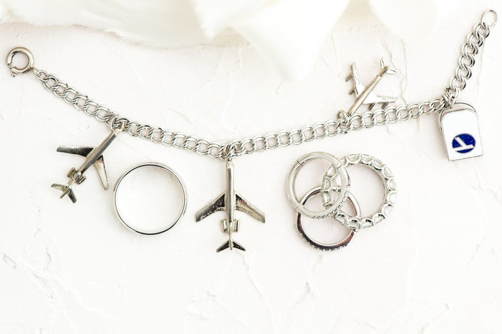 planes and pilot charm bracelet and wedding and engagement rings styled flat lay