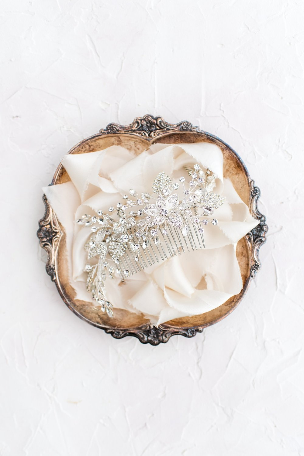 Styled flat lay of crystal bridal headpiece on vintage silver tray
