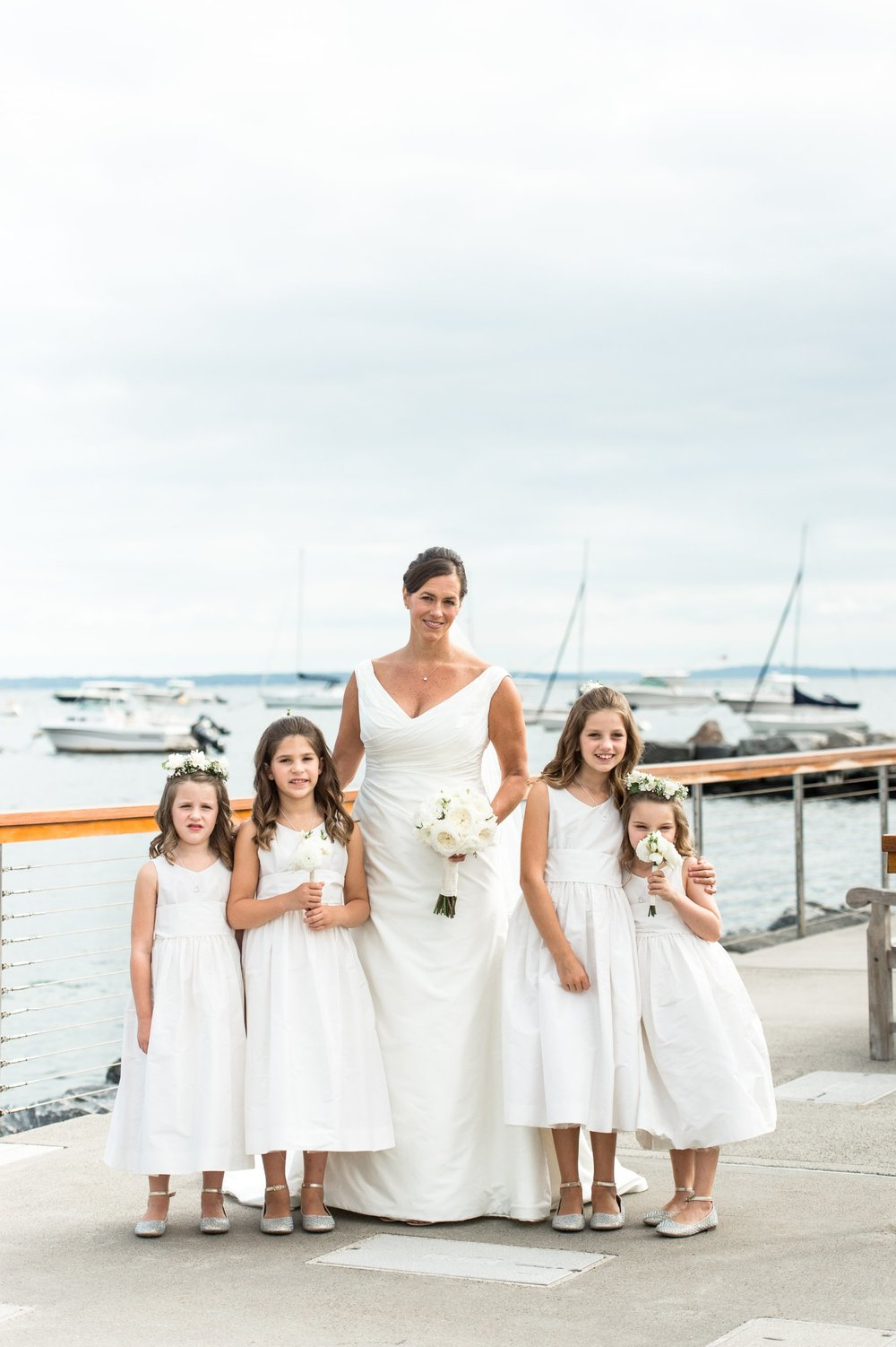 Bride in Augusta Jones dress with four little flower girls in white jcrew dresses pose on docks at Belle Haven Club for fall nautical inspired wedding